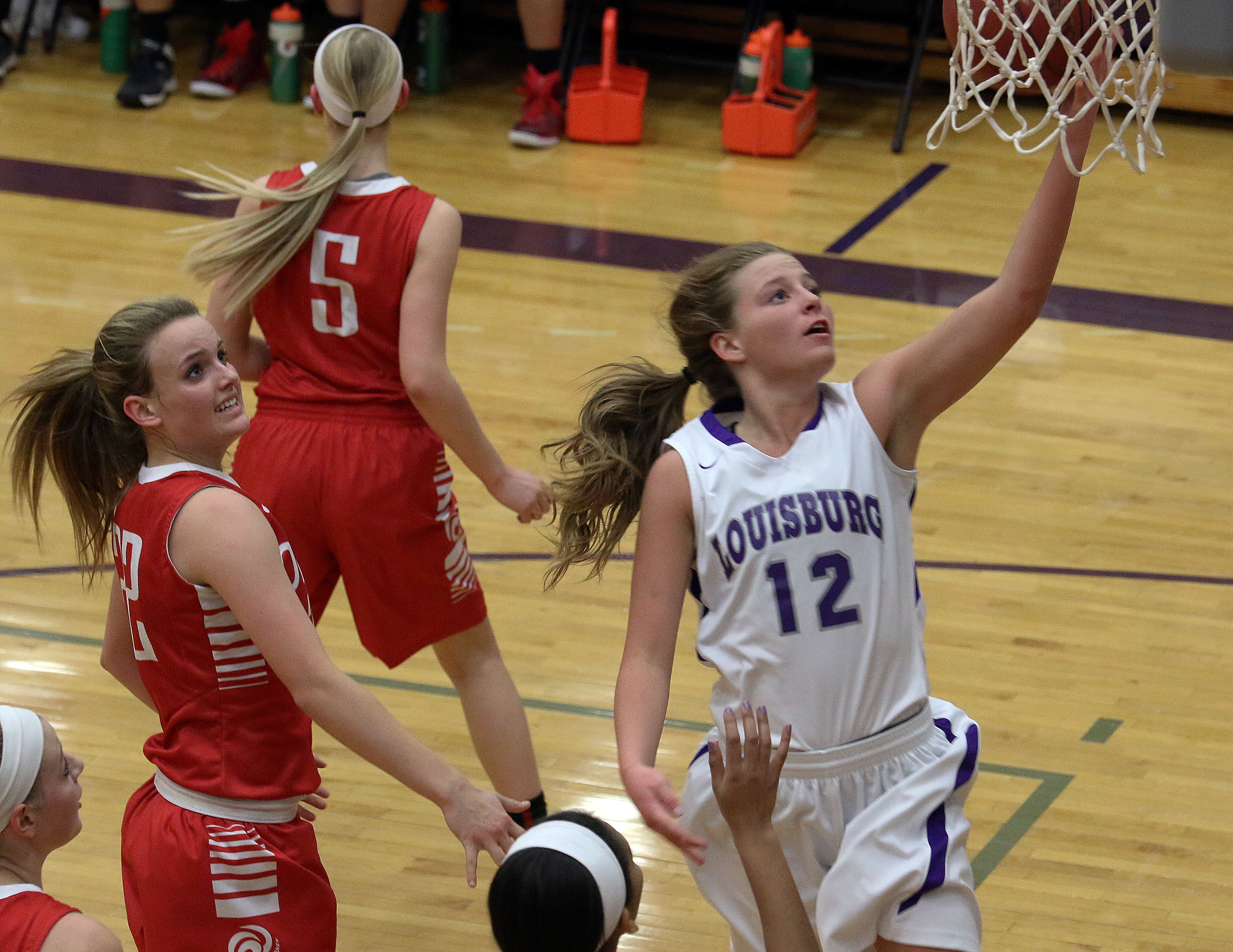 Louisburg junior Natalie Moore drives past an Ottawa player to the basket Friday in Louisburg. Moore finished with 27 points in the 60-51 loss