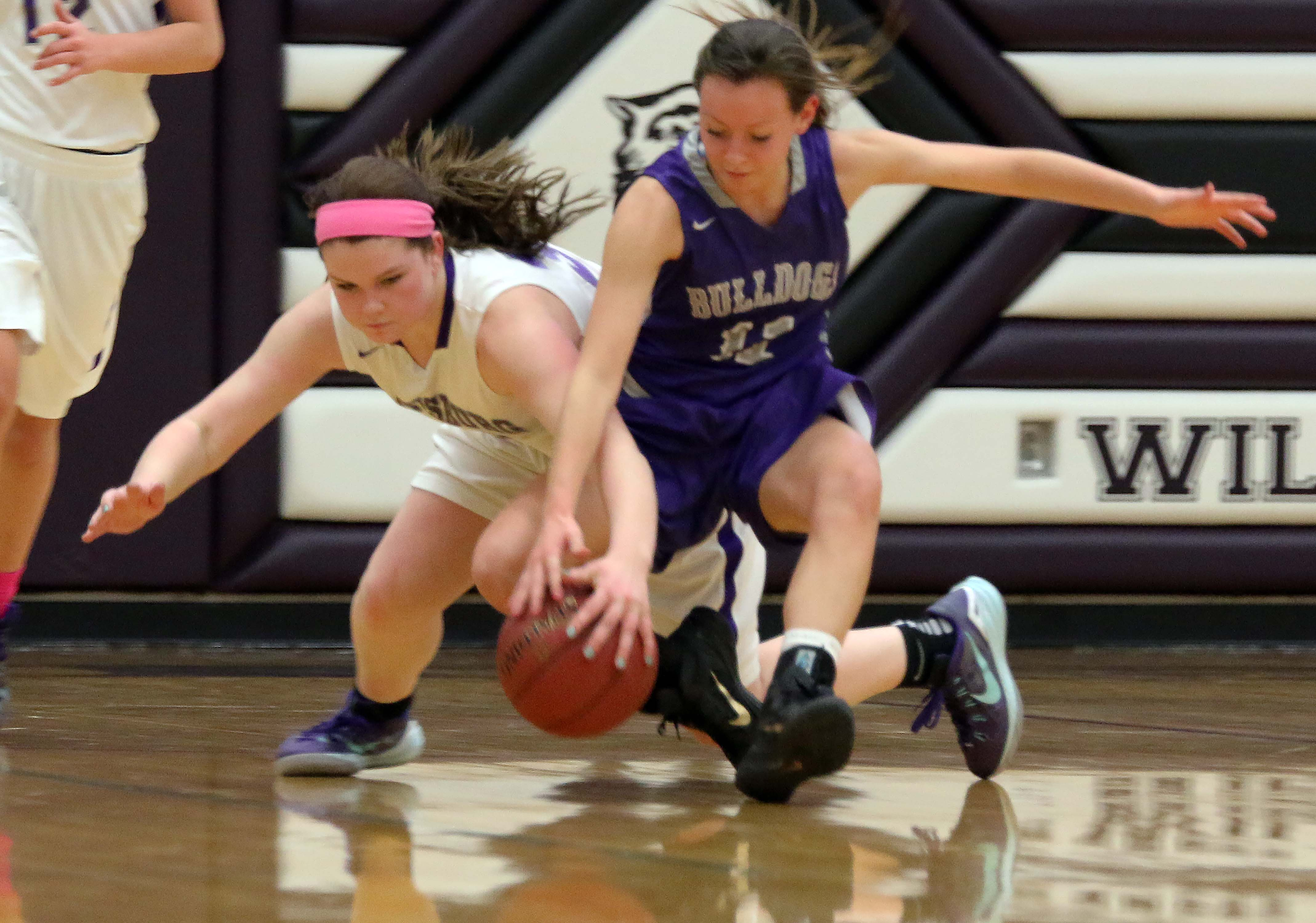 Louisburg's Kallie O'Keefe (left) dives on the floor for a loose ball Tuesday in Louisburg. O'Keefe finished with seven points and seven rebounds.