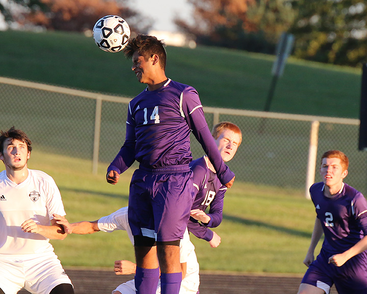 Eric Vazquez heads the ball away during Thursday's game against Paola.