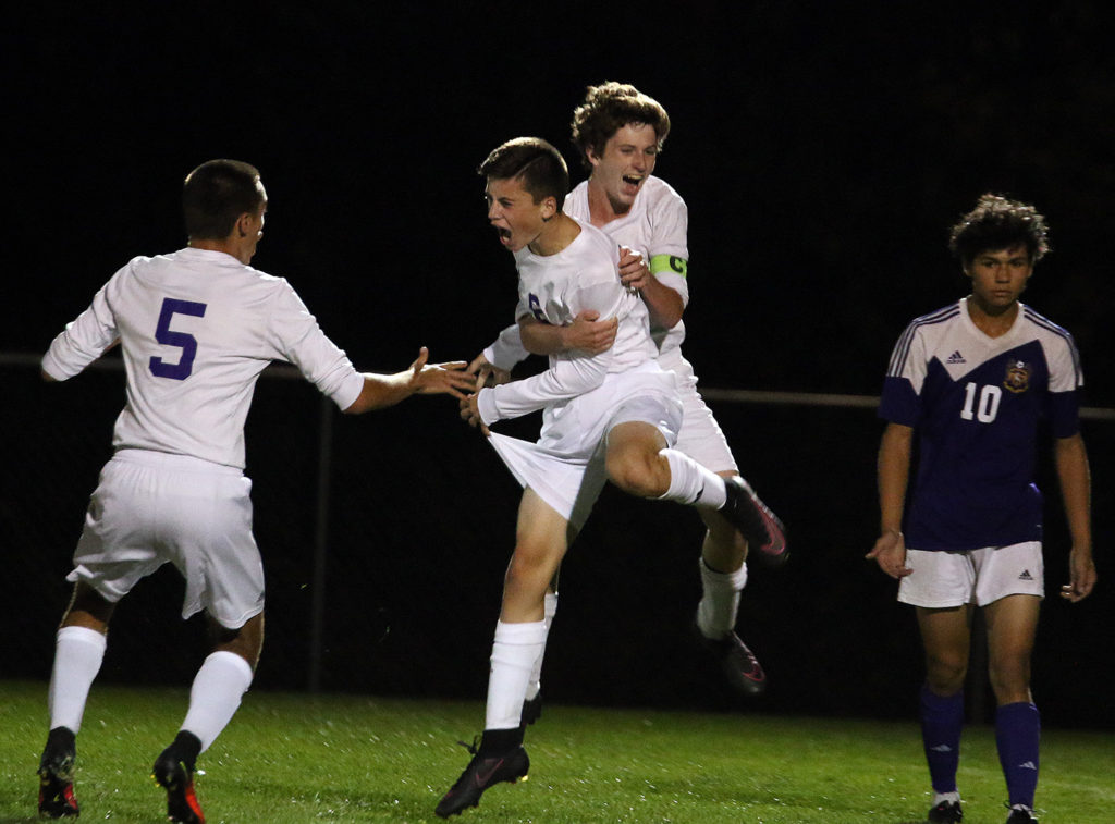 Landon Johnson celebrates his game-tying goal with teammates Grant Ryals (on back) and Herman Knipp on Monday in Louisburg.