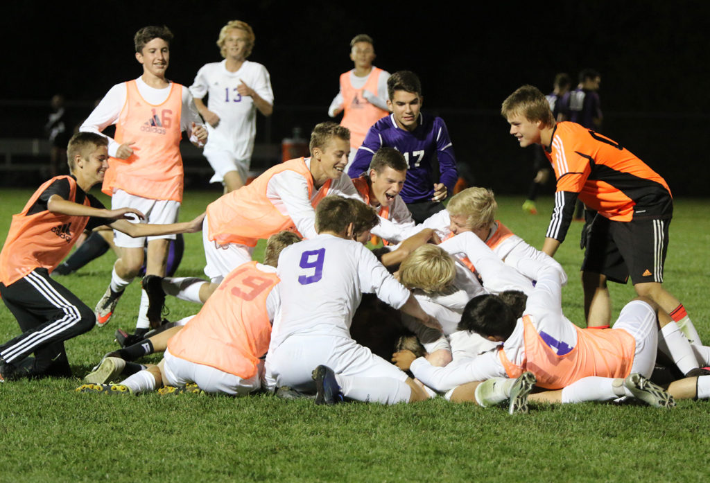 Members of the Louisburg High School soccer team dogpile on teammate Grant Ryals after he scored the game-winning goal in the second overtime Tuesday in Louisburg.
