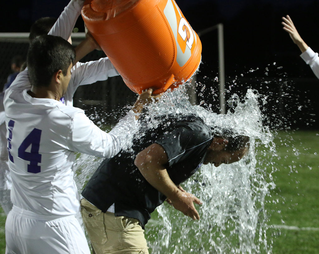 Louisburg head coach Kyle Conley is doused with cold water thanks to Herman Knipp and Eric Vazquez (14) following Tuesday's win.