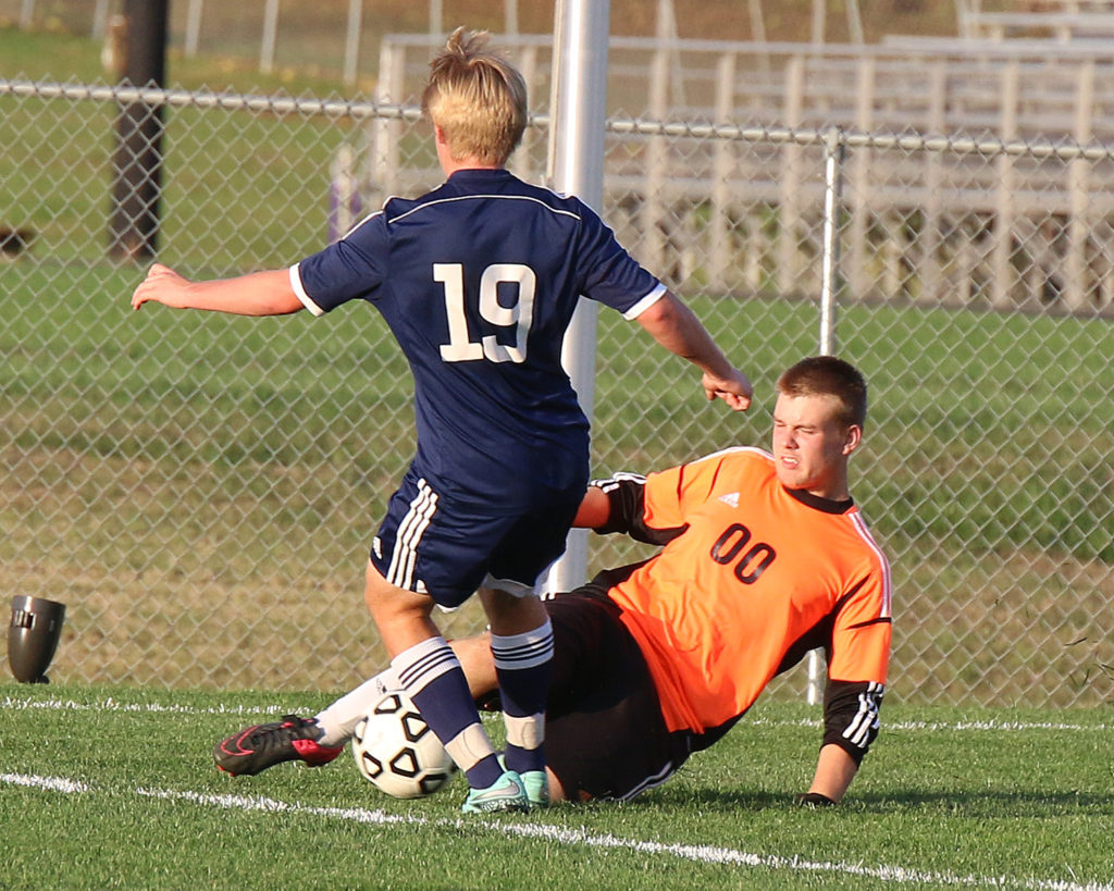 Louisburg goalie Ambrose Stefan slides in for one of his many saves Tuesday in the state quarterfinals in Louisburg.