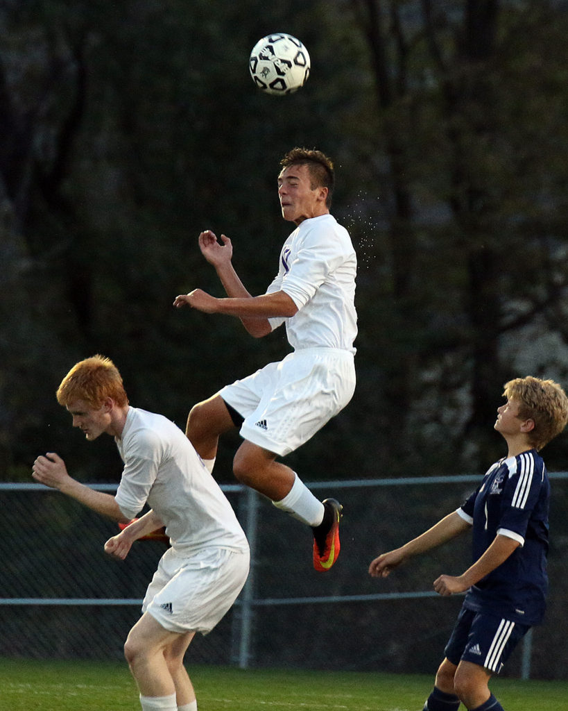 Junior defender Kris Light heads the ball away during Tuesday's state quarterfinal match against Trinity.